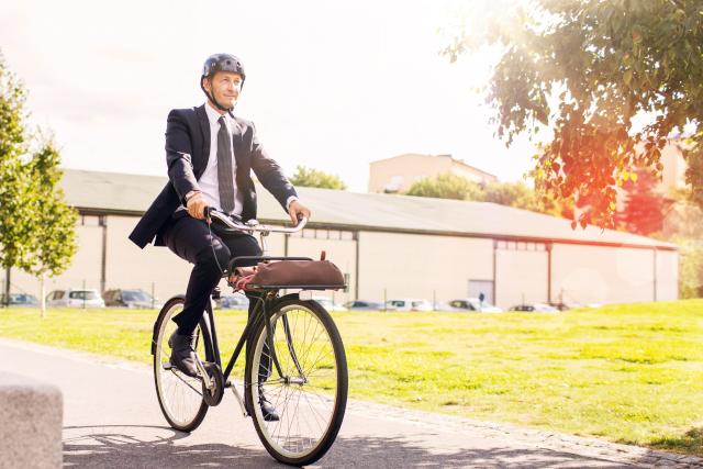 Ein Mann im Anzug fährt mit einem Fahrrad durch einen Park.