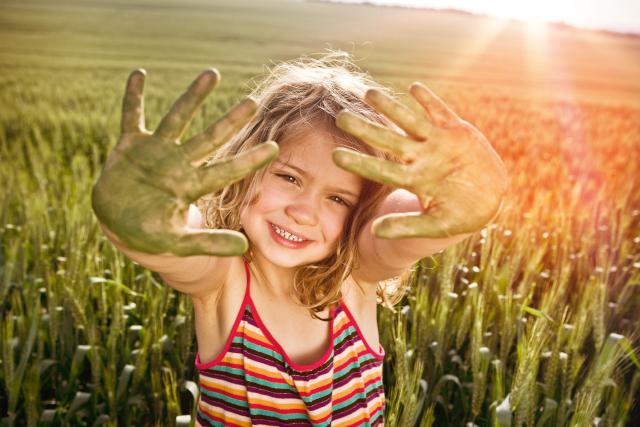 Ein Kind spielt im Feld und hält seine schmutzigen Hände in die Luft.