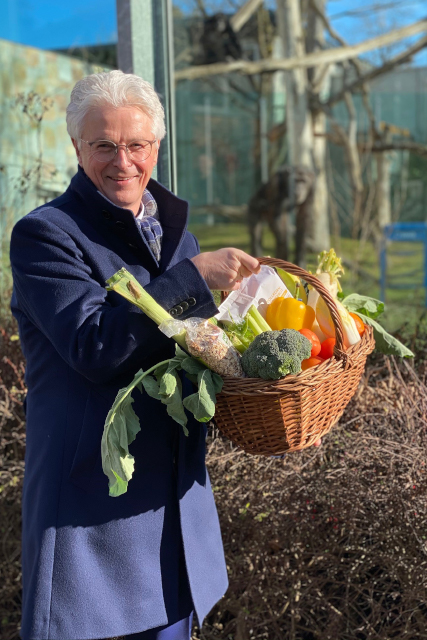 Der Vorstandsvorsitzende der Stadtsparkasse Augsburg, rolf Settelmeier hält einen Korb mit Gemüse für die Schmpansen in der Hand.